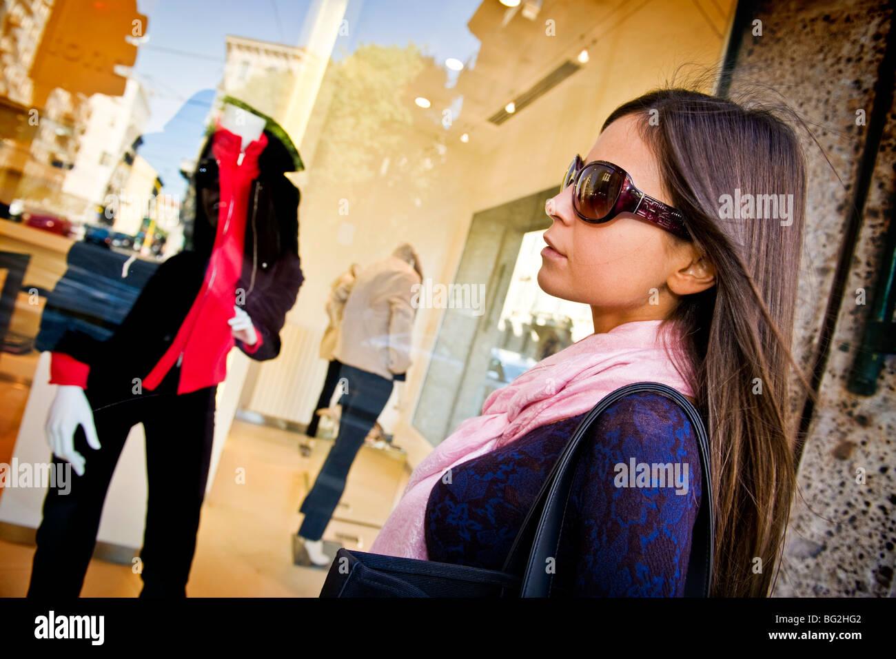 Giovane donna alla ricerca di un negozio, Milano, Italia Immagini Stock