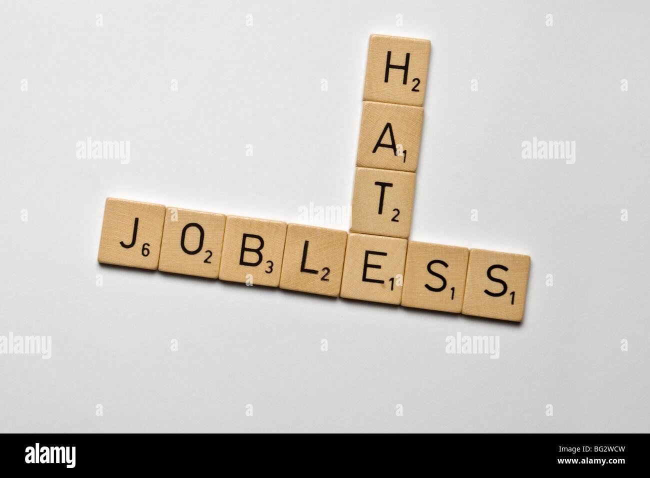 Pietre di scrabble scritto disoccupati e odio Immagini Stock