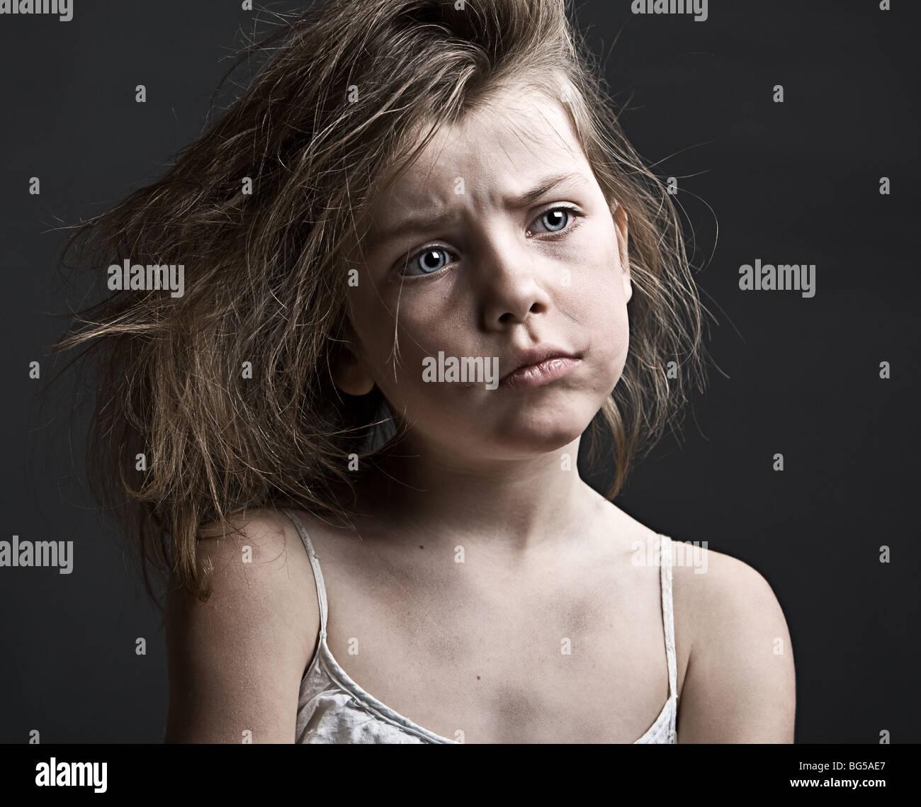 Potente colpo di un confuso bambino contro uno sfondo grigio Immagini Stock