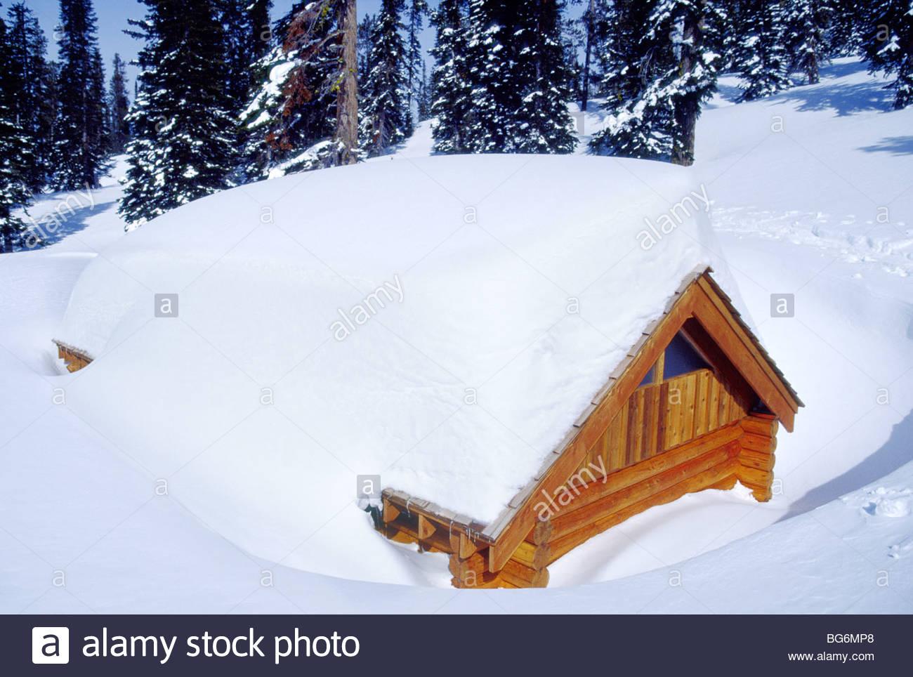 L'Alaska. Tradizionale Log Cabin quasi sepolto dalla neve pesante caduta in inverno. Immagini Stock