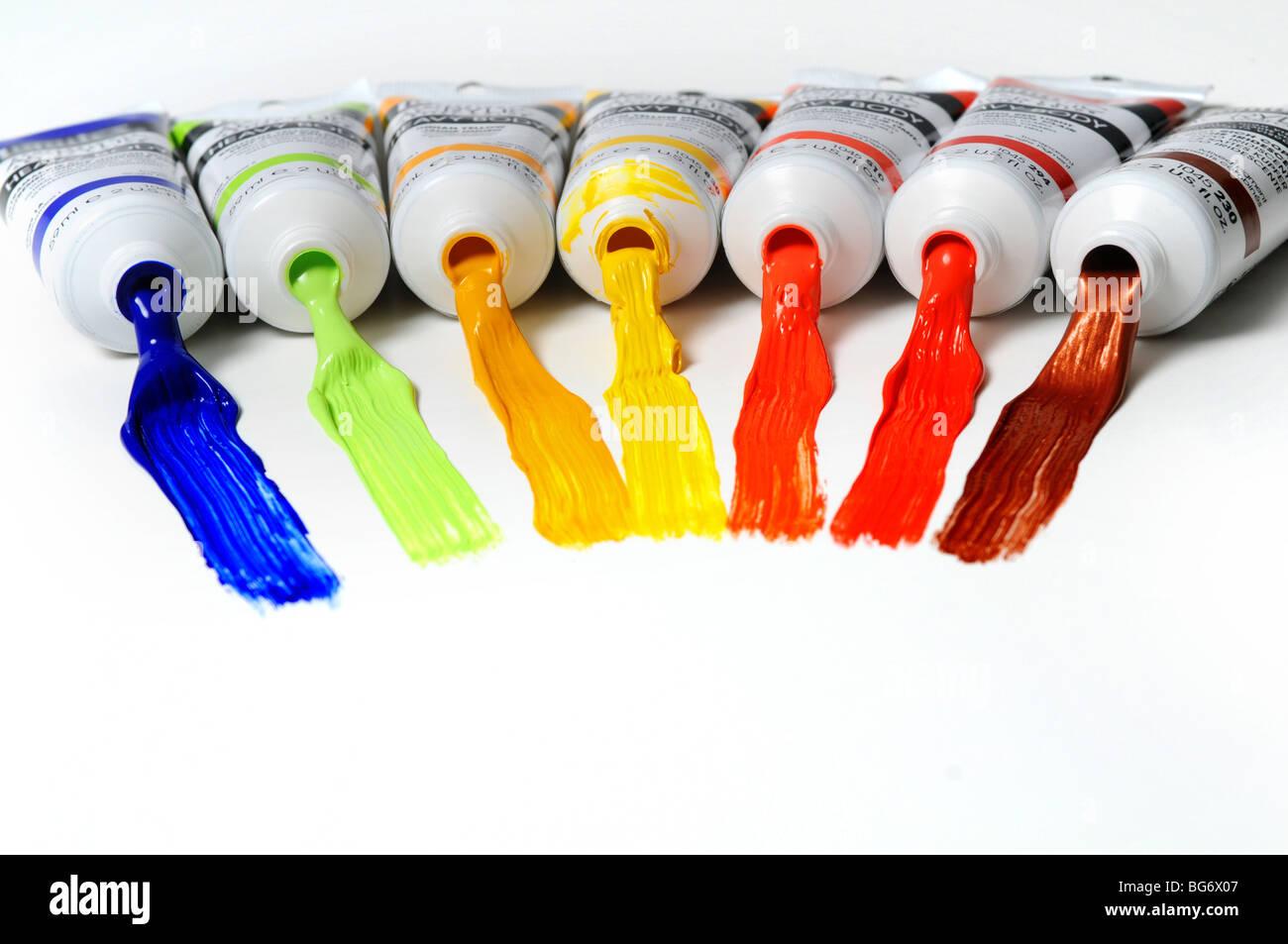 Tubi di vernice con colori diversi si sviluppa su di una superficie bianca Immagini Stock