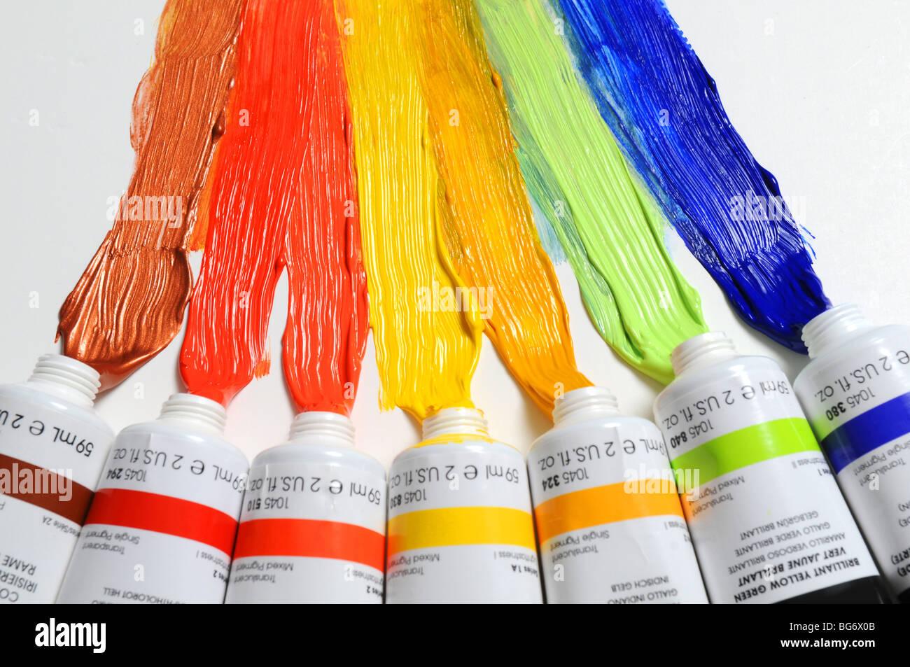 La vernice di diversi colori sparsi su uno sfondo bianco Immagini Stock