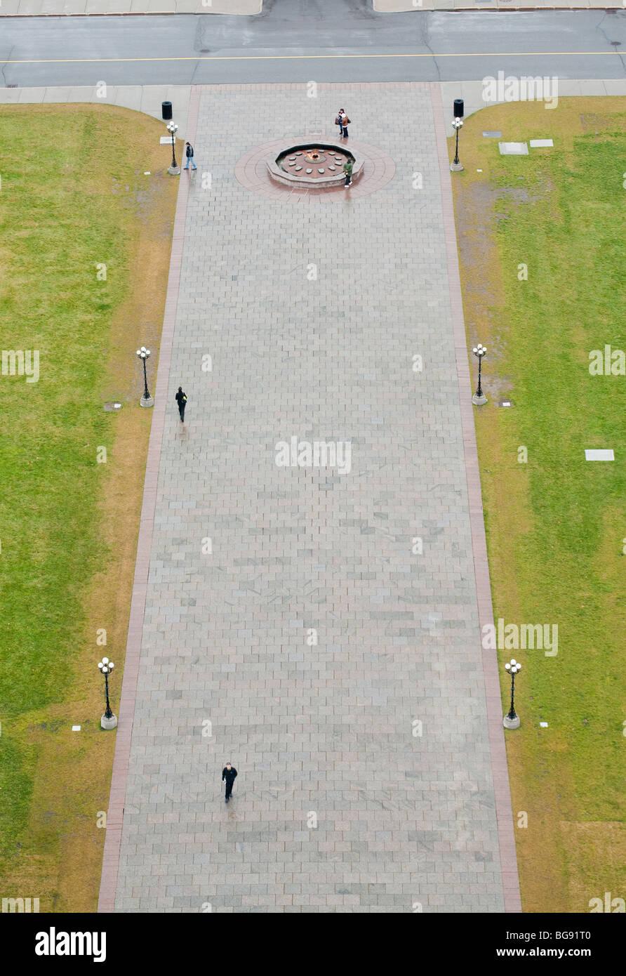 Approccio al Parlamento. La fiamma eterna da la torre della pace in un giorno di pioggia. 6 turisti camminare circa. Immagini Stock