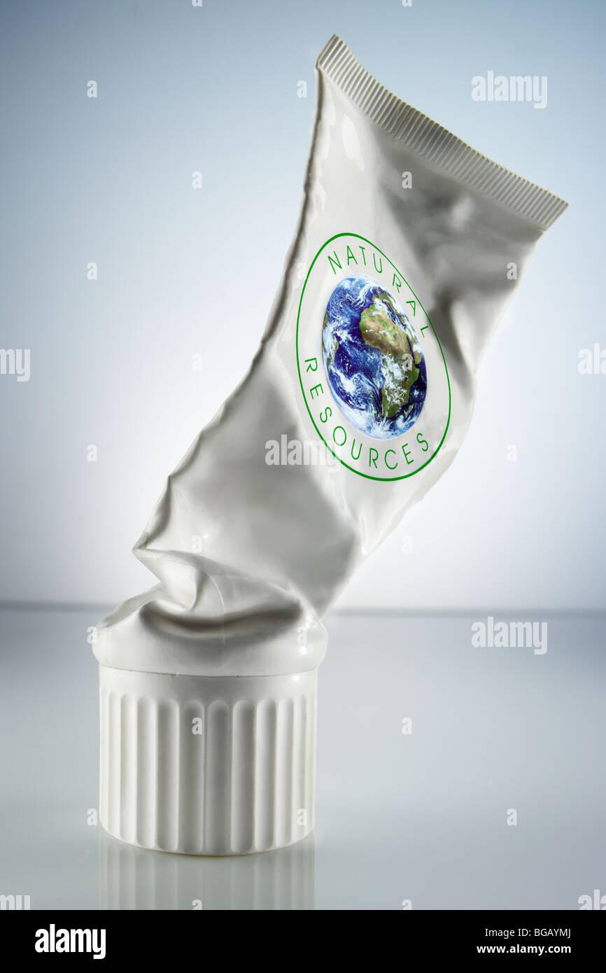 Spremuto-out tubo bianco contrassegnato con le parole delle risorse naturali e un globo Immagini Stock