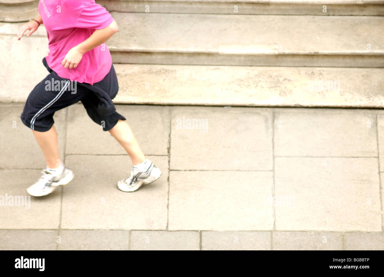 Royalty free fotografia della donna in esecuzione nella sua ora di pranzo sul marciapiede London REGNO UNITO Immagini Stock