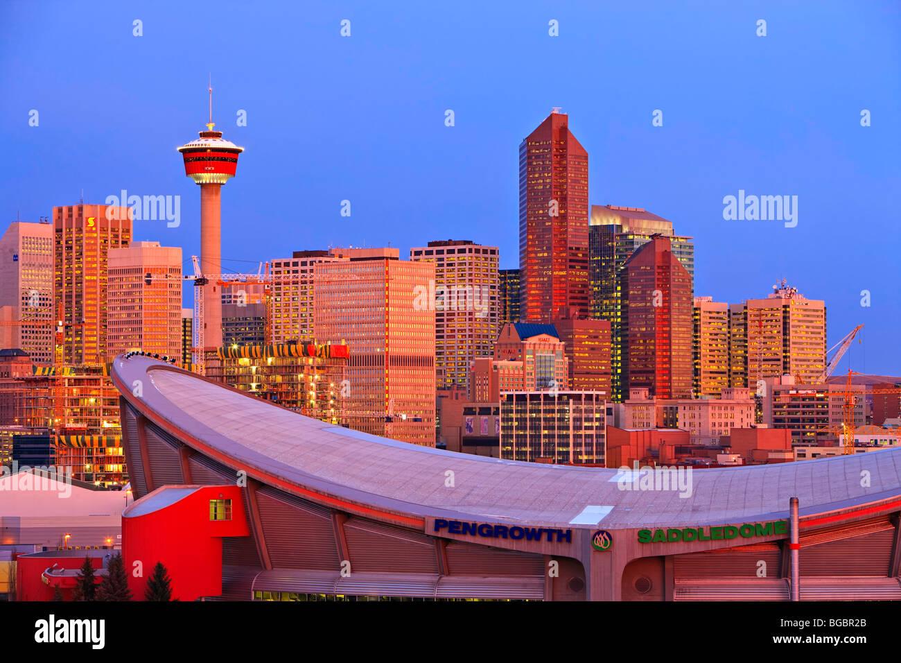 Il Saddledome con edifici ad alta e la Torre di Calgary in background di sunrise, città di Calgary, Alberta, Immagini Stock