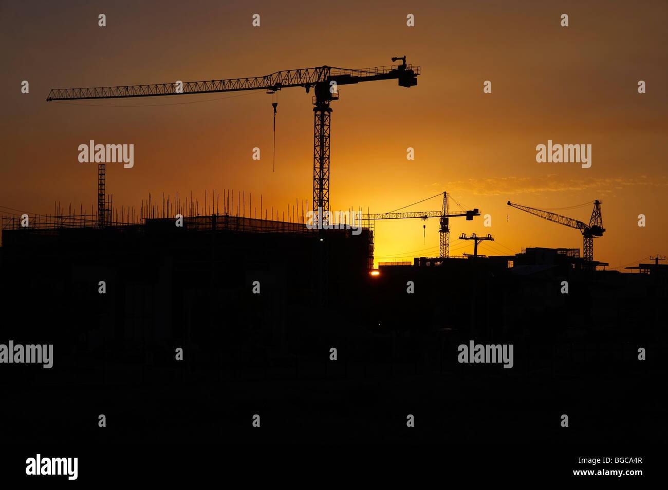 Gru a torre stagliano su un sito in costruzione Immagini Stock