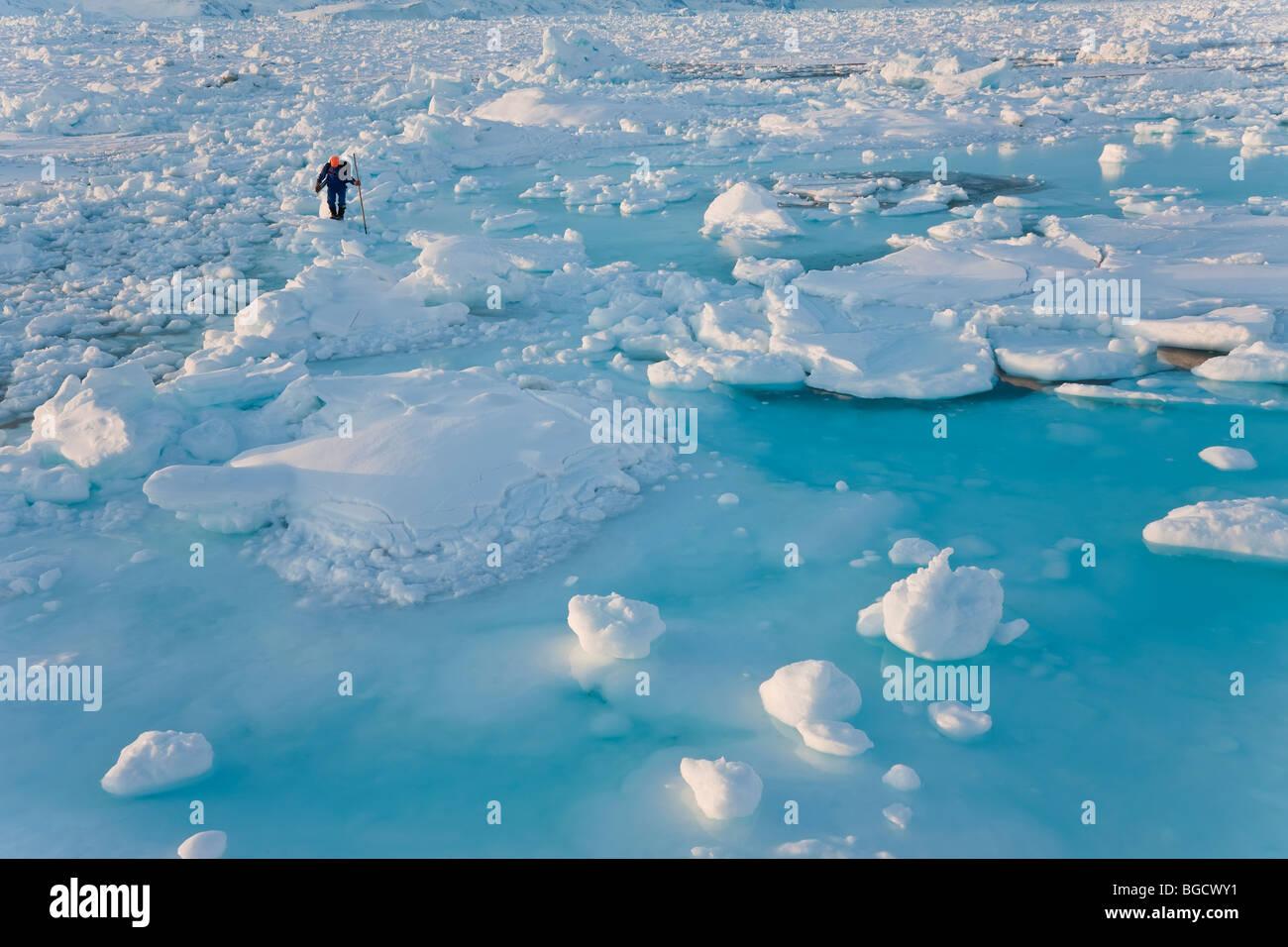 Il cacciatore di tenuta sul mare di ghiaccio, Tiniteqilaq, E. Groenlandia Immagini Stock