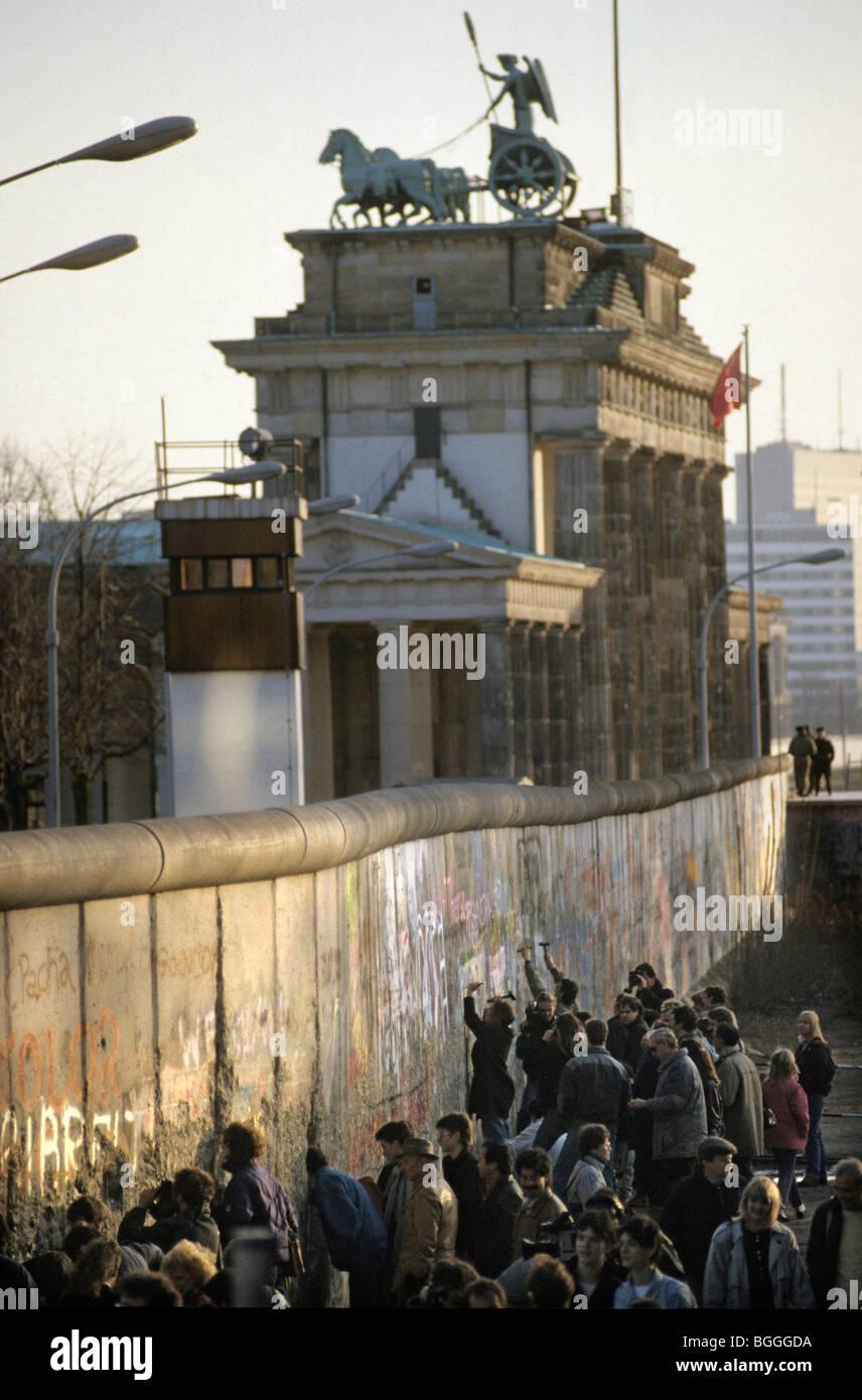 Caduta del muro di Berlino: persone scalpellatura parti fuori del muro alla porta di Brandeburgo, Berlino, Germania Immagini Stock