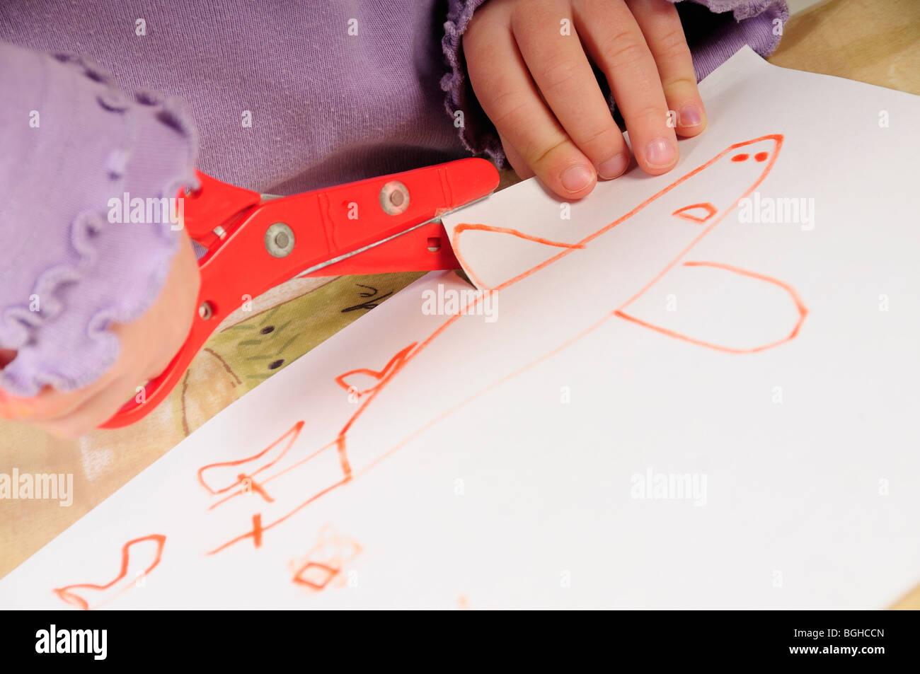 Foto di stock di un 4 anno vecchia ragazza di ritagliare una foto che ha appena disegnato su un pezzo di carta. Immagini Stock