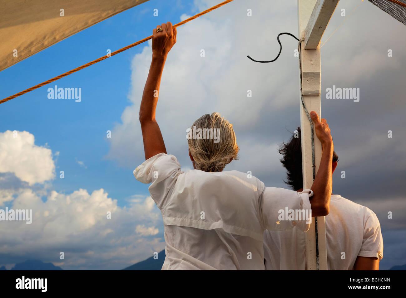 Due persone che guardano verso l'orizzonte dalla parte anteriore di una imbarcazione; PALAWAN FILIPPINE;. Immagini Stock