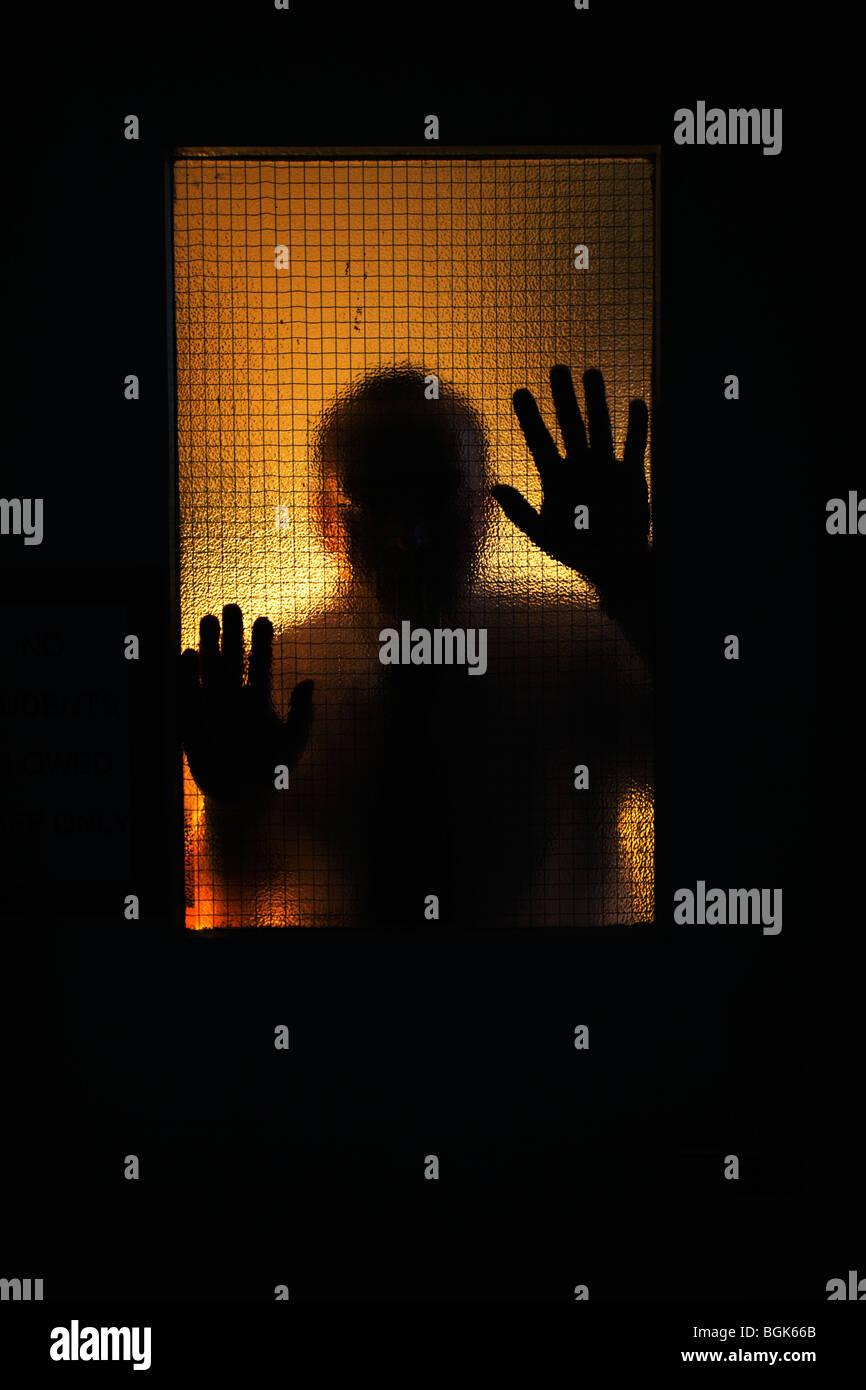 Man mano tiene contro il filo di vetro rinforzato fire finestrino di portiera. Immagini Stock