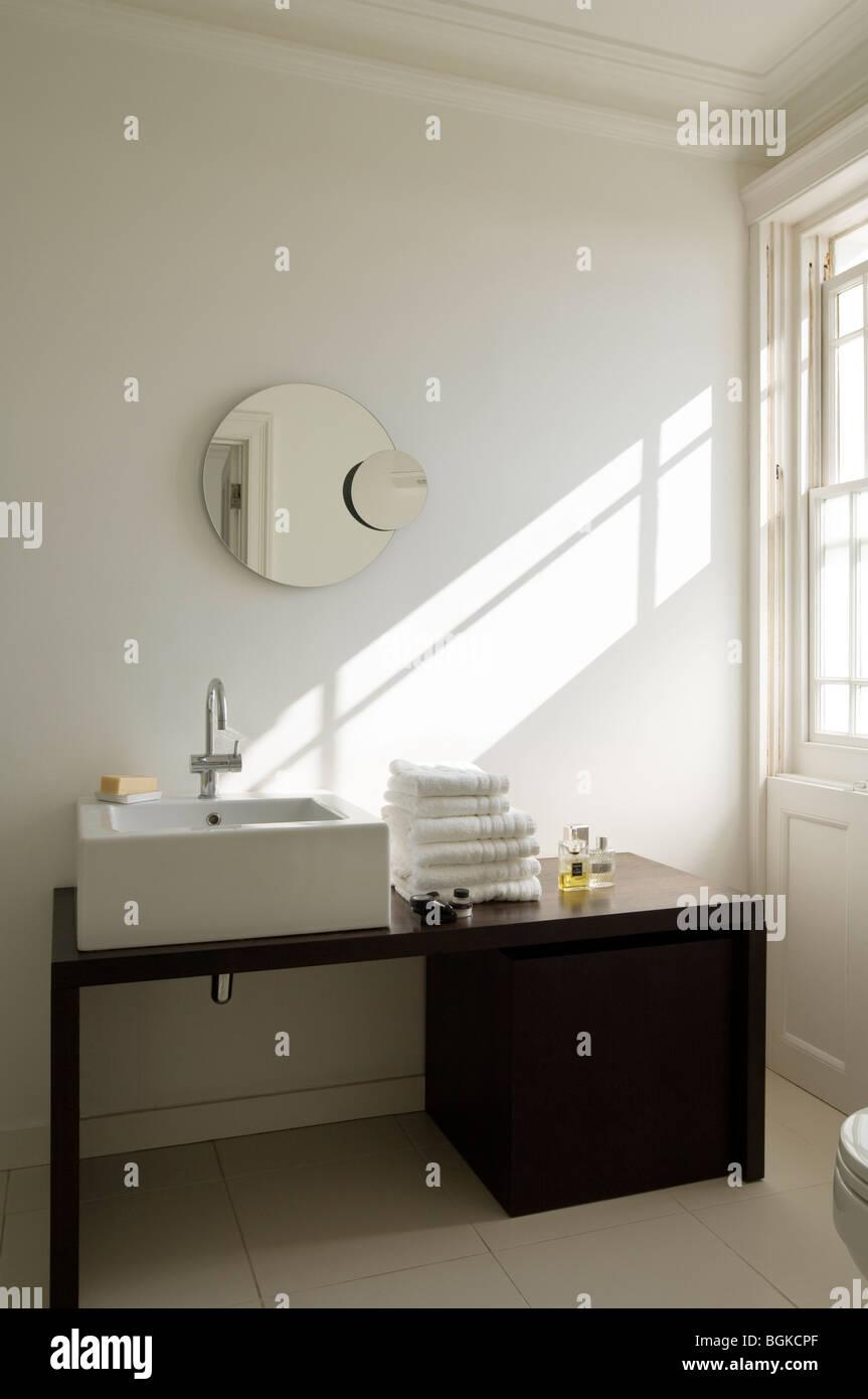 Bagno moderno con nero lavandino e specchio rotondo Foto Stock