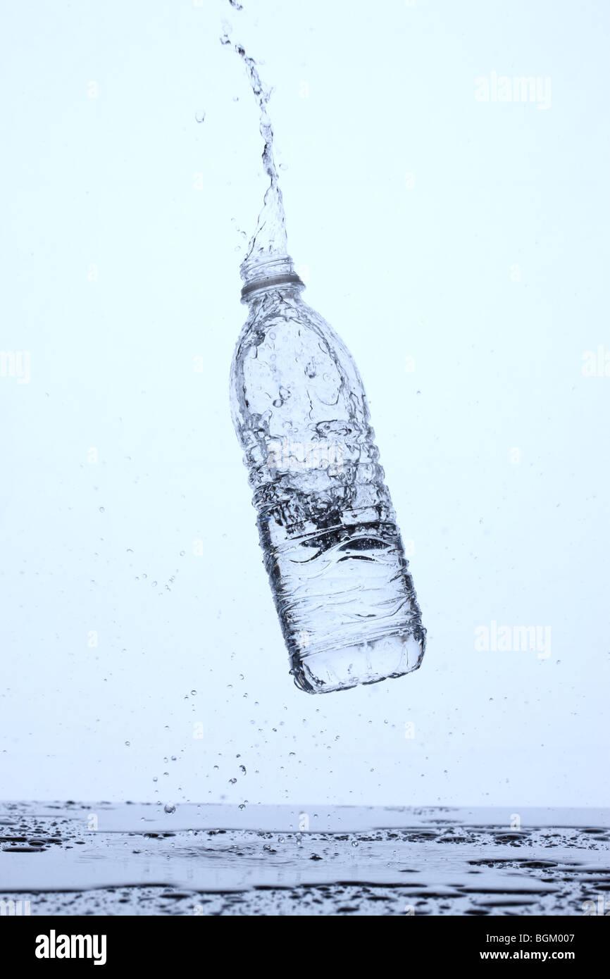 Bottiglia di acqua rimbalzante su superficie e schizzi Immagini Stock