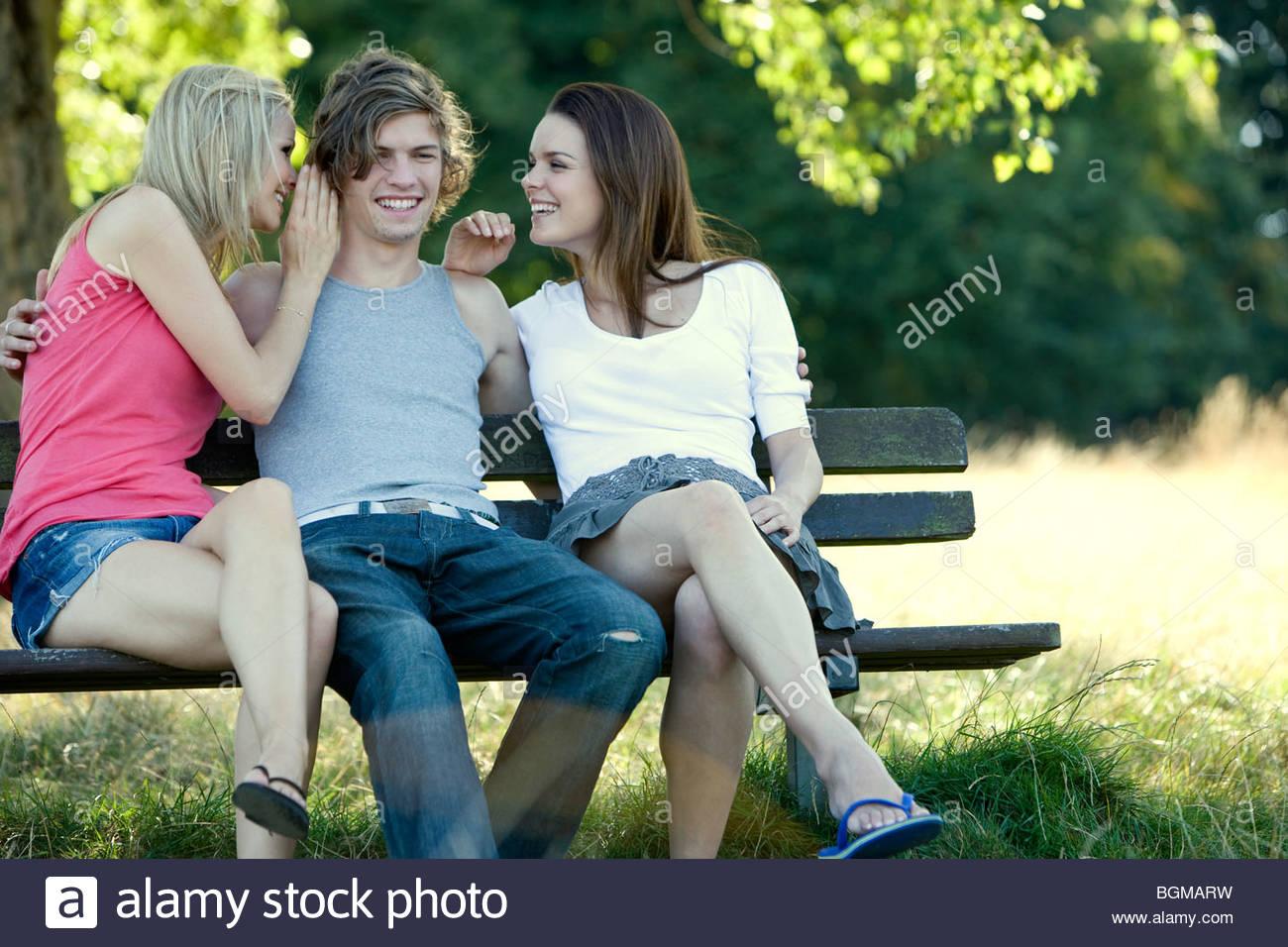 Un giovane uomo su un banco di lavoro, due giovani donne whispering a lui Immagini Stock