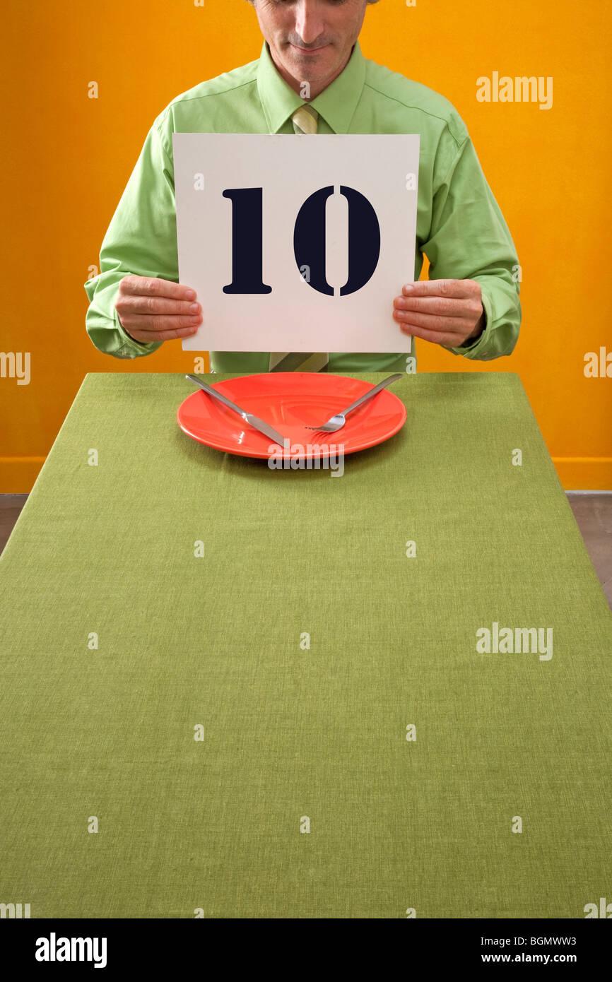 Uomo di mangiare a tavola può contenere fino a 10 segno alla cena di velocità Immagini Stock