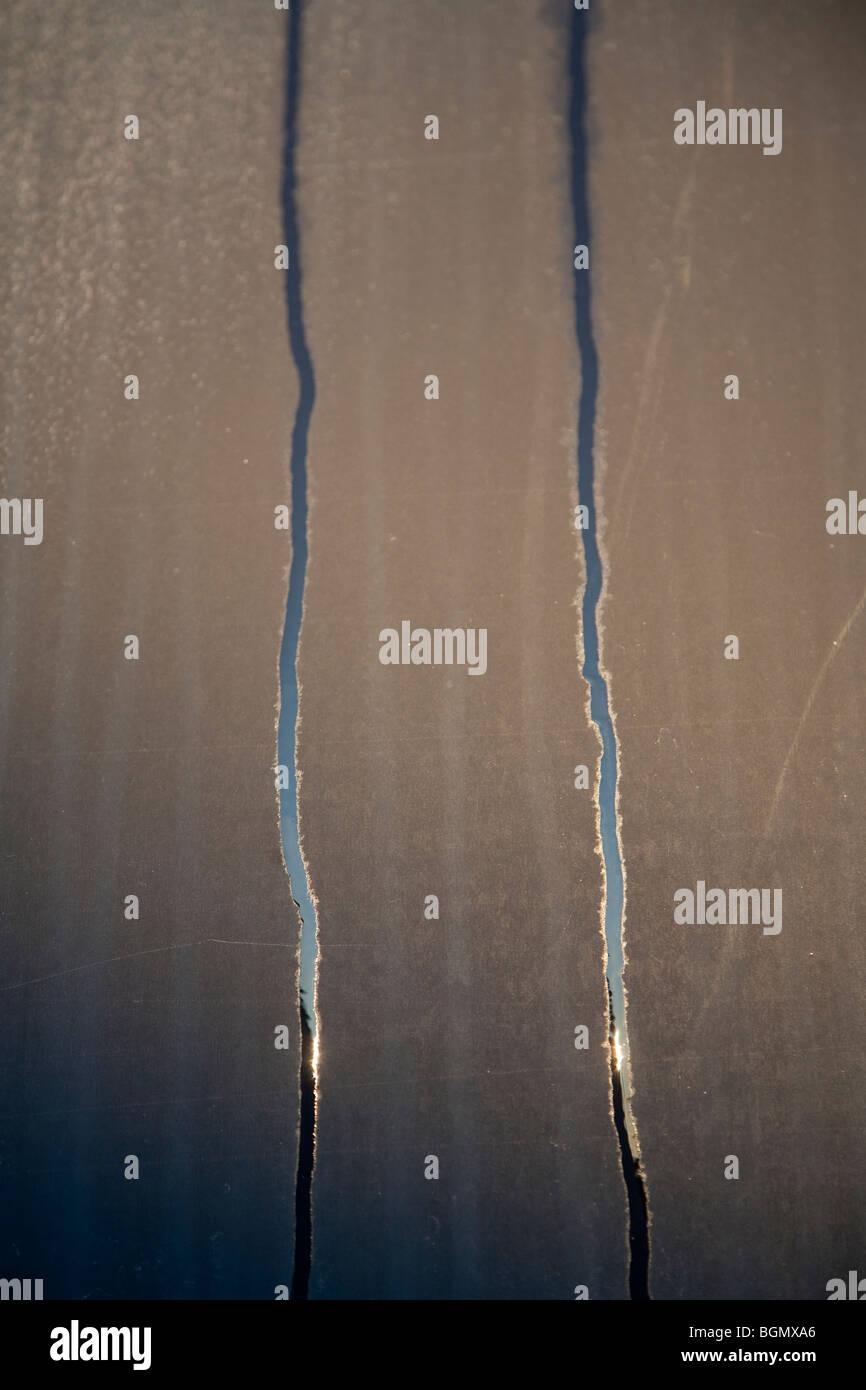 Rivoli di passo che scorre sulla scura opaca superficie metallica Immagini Stock