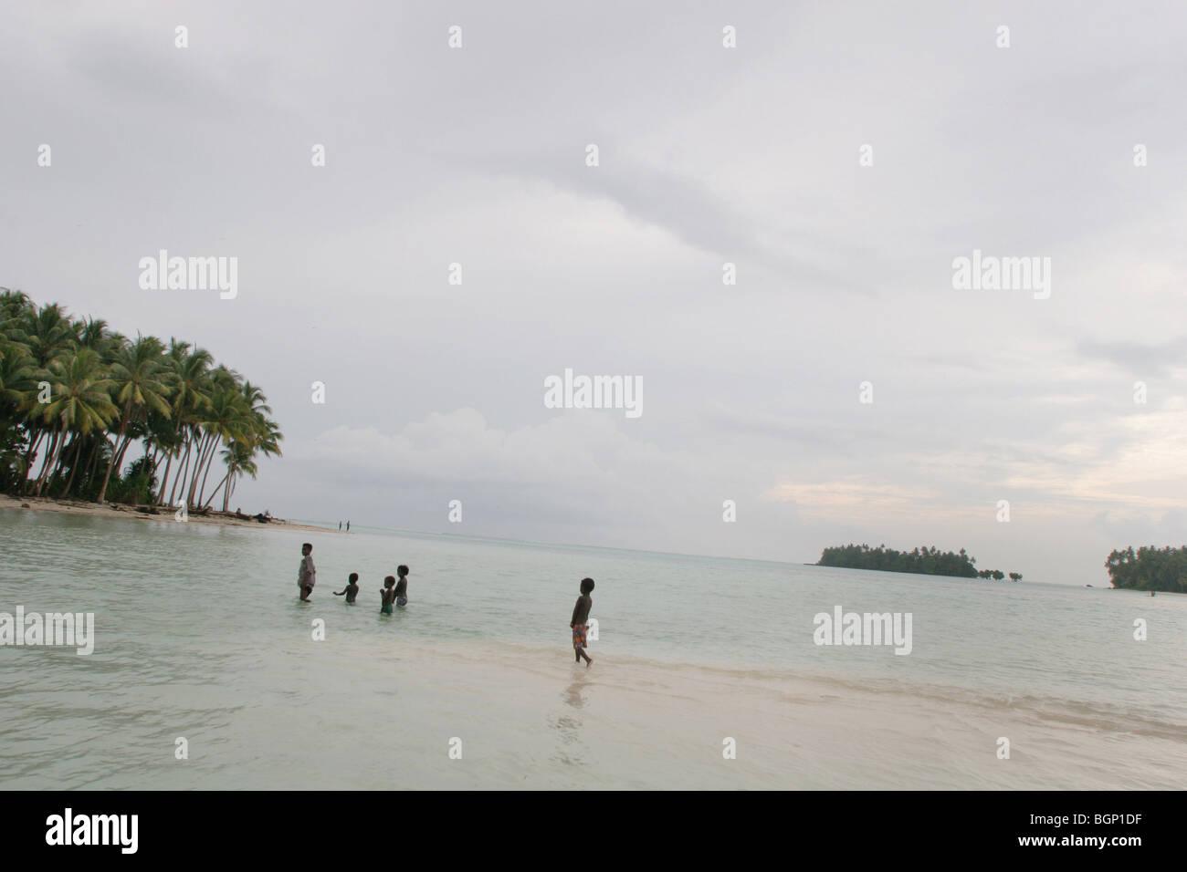Bambini da Iolasa Isola a piedi su un poco profondo banco di sabbia, Carterets Atoll, Papua Nuova Guinea Immagini Stock