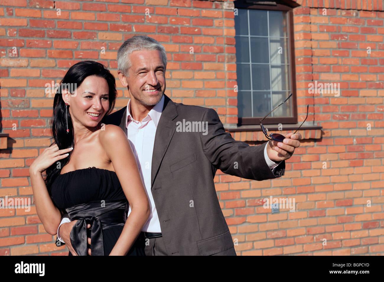 Attraente coppia felice in piedi accanto al muro di mattoni Immagini Stock
