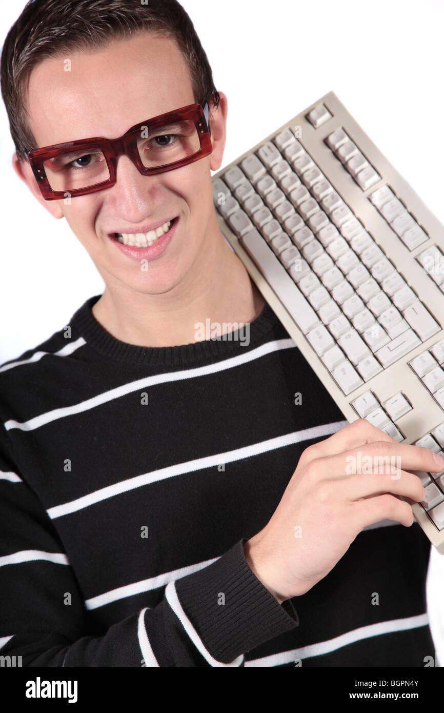 Un tipico nerd tenendo una tastiera. Tutti gli isolati su sfondo bianco Immagini Stock