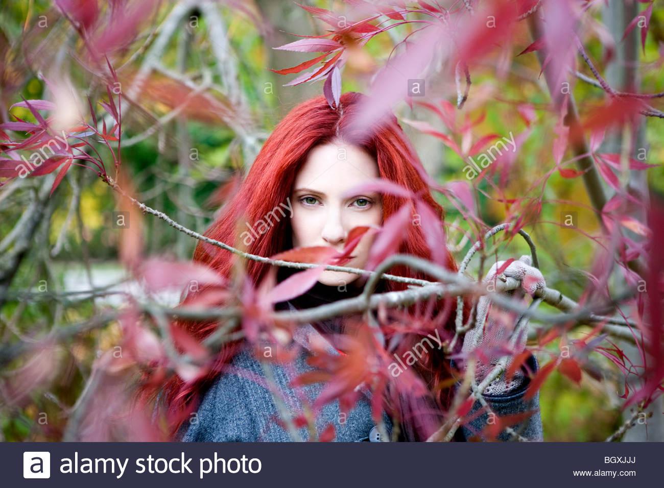 Una giovane donna in piedi tra gli alberi in autunno Immagini Stock