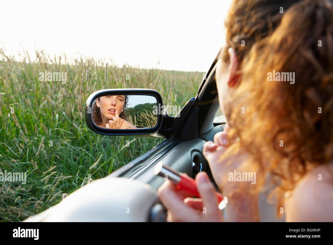 La riflessione della donna in specchietto retrovisore Immagini Stock