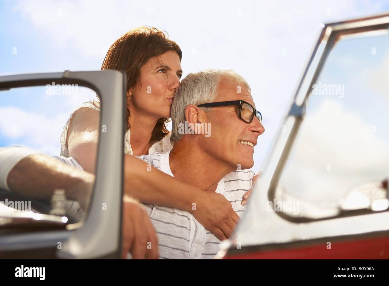 Coppia senior abbracciando in auto sportiva Immagini Stock