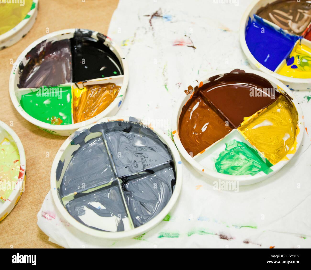 Vernice per bambini in tavolozze di miscelazione su un tavolo Immagini Stock