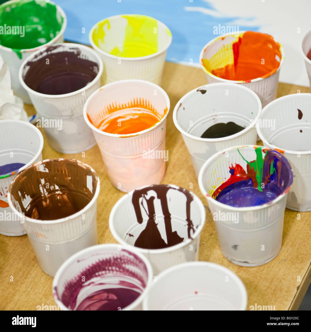 I bicchieri di plastica piena di bambini la vernice su un tavolo di legno Immagini Stock