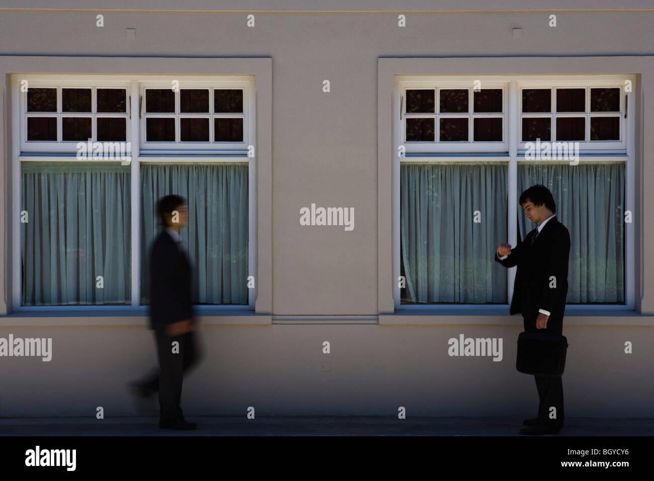 Giovane imprenditore in piedi sul marciapiede, controllando il tempo come un altro uomo si avvicina Immagini Stock