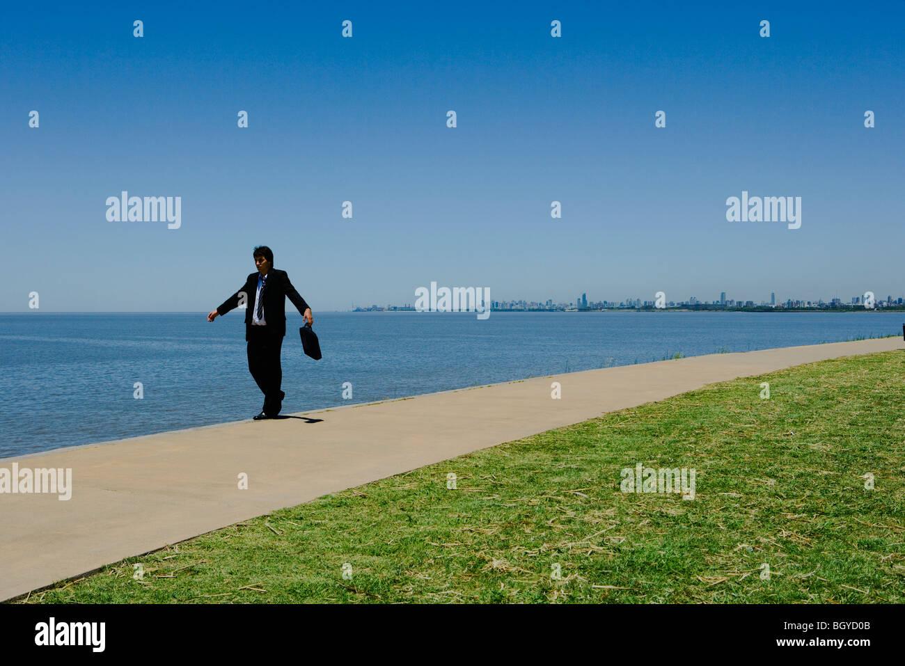 Imprenditore camminando lungo il bordo del marciapiede lungo mare, braccia Immagini Stock