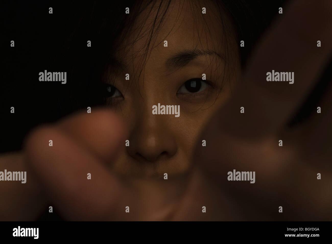Donna con le mani alzate in difesa, oscurando il volto Immagini Stock