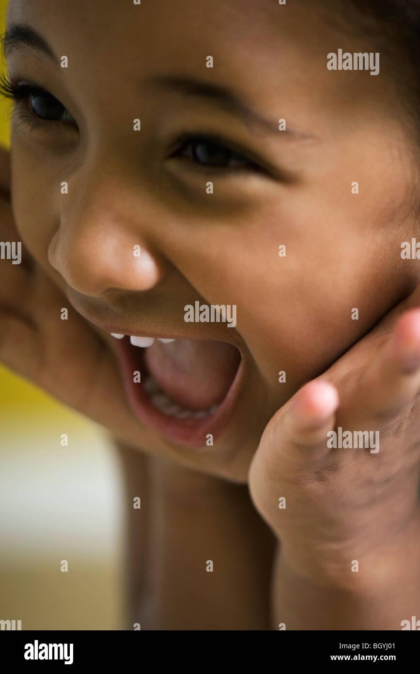 Bambina tenendo le mani per affrontare con sguardo di sorpresa Immagini Stock