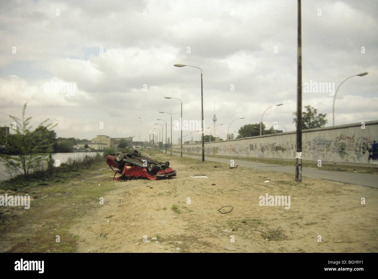 Una vettura si siede ribaltato e abbandonato nei pressi del muro di Berlino nel maggio del 1991, poco prima del Immagini Stock