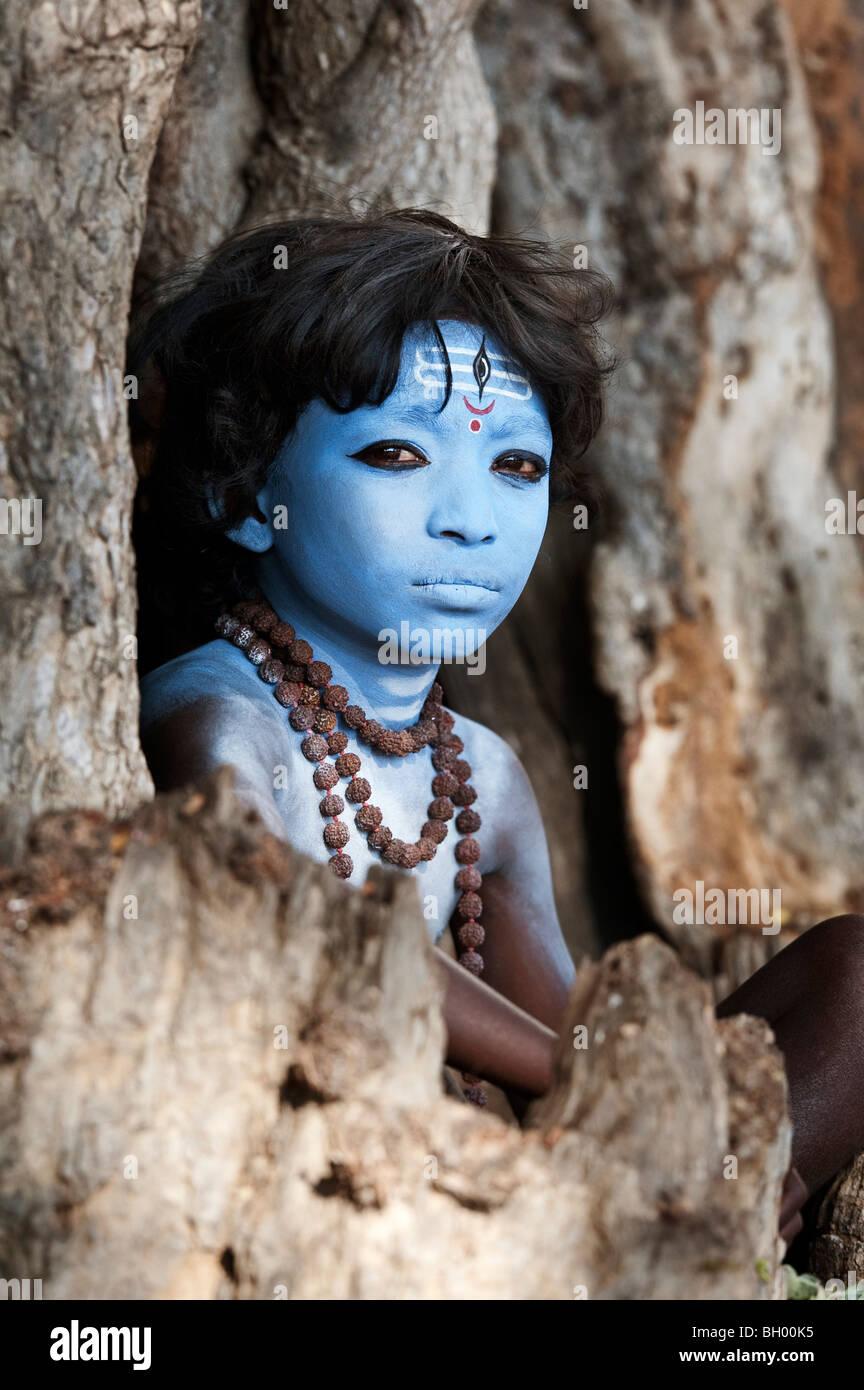Ragazzo indiano, faccia dipinta come il dio indù Shiva seduto in un vecchio ceppo di albero. Andhra Pradesh, Immagini Stock