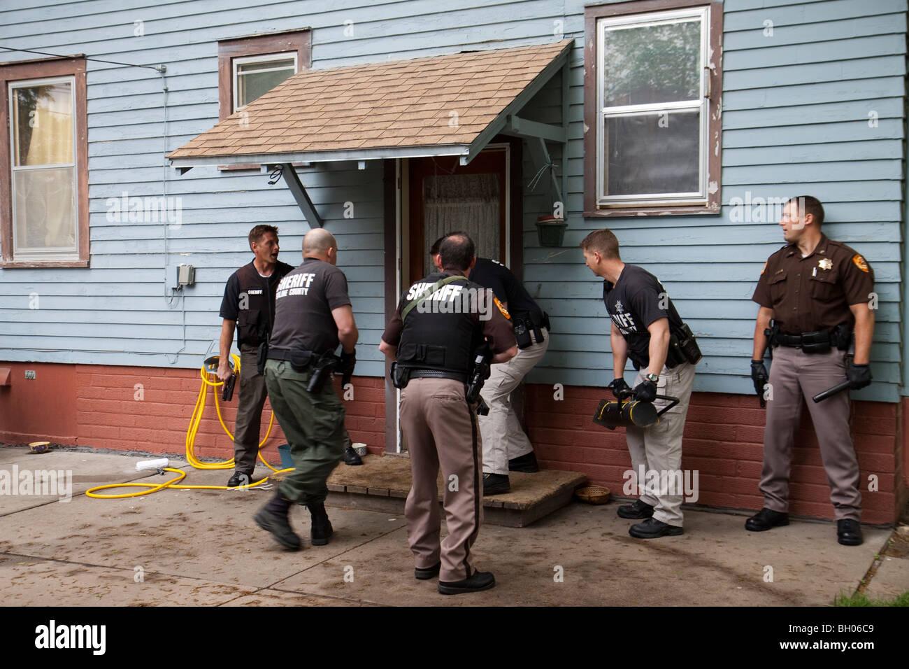 Sheriff's Office deputati che serve in materia di lotta contro la droga di un mandato di perquisizione. Immagini Stock
