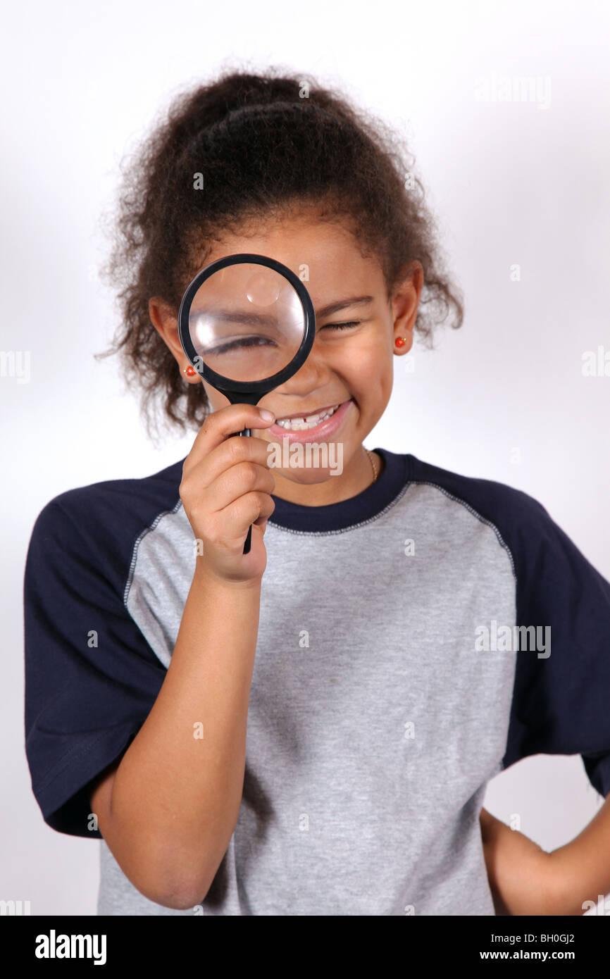 Ragazza afro-americana guardando attraverso una lente di ingrandimento Immagini Stock