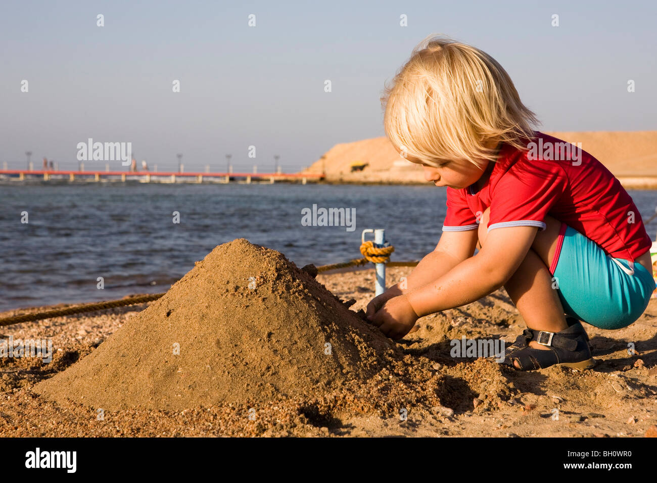 Piccolo bambino, ragazza, 3, che gioca con la sabbia sulla spiaggia del Lamaya Resort, Coraya, Marsa Alam, Mar Rosso, Immagini Stock