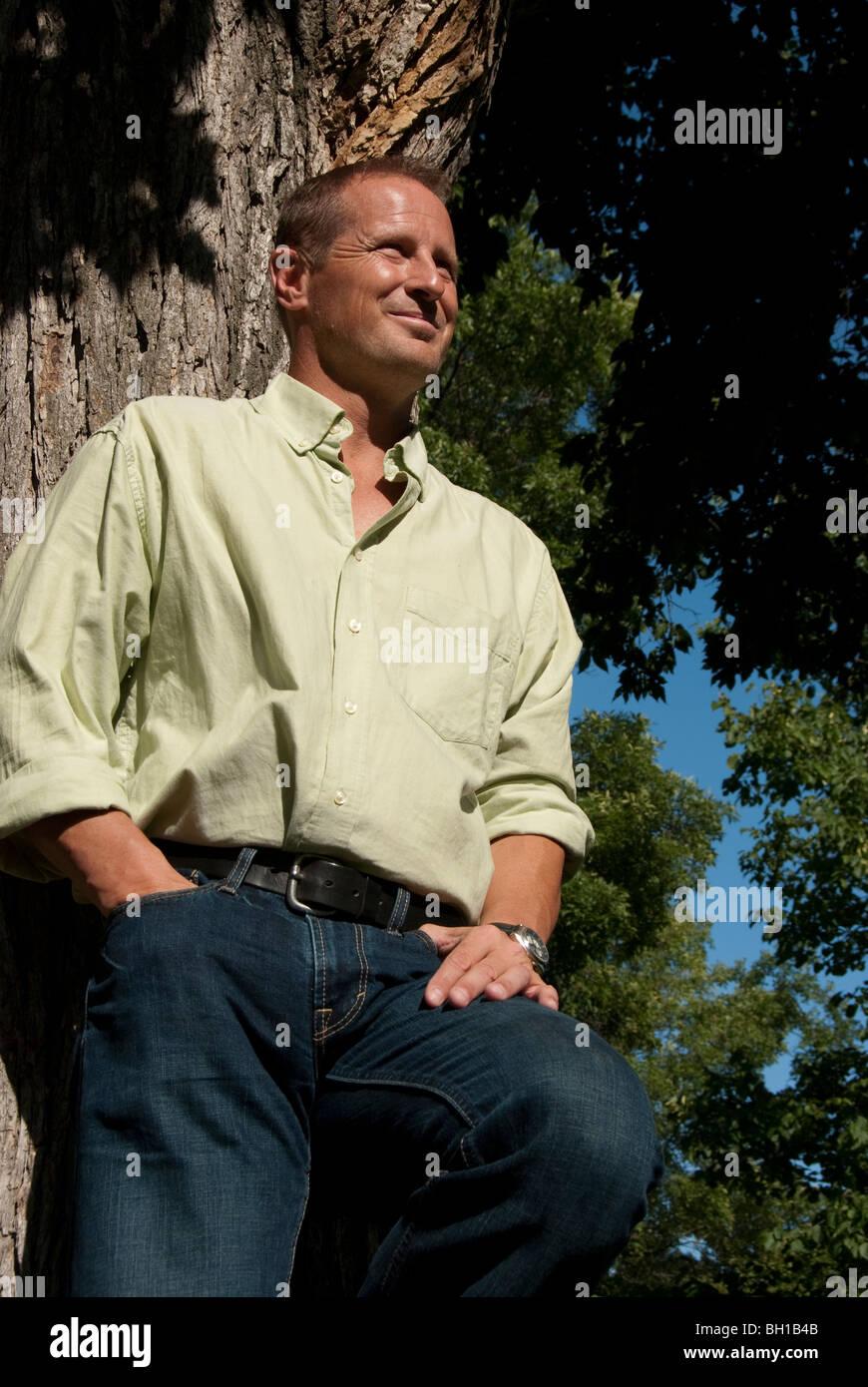 Basso angolo di visione dell uomo in 40's appoggiata ad albero, Assiniboine Park, Winnipeg, Manitoba, Canada Immagini Stock