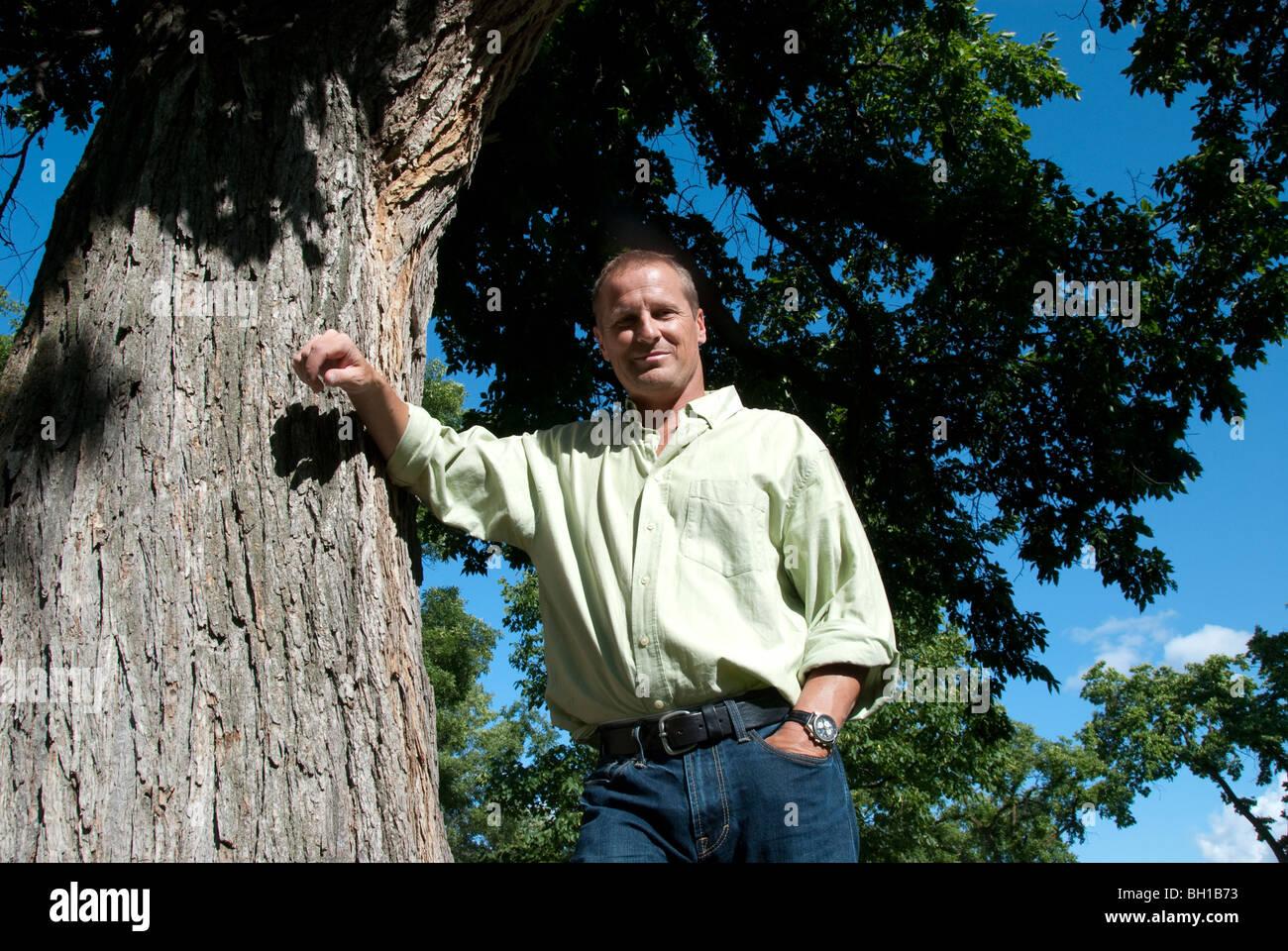Basso angolo di visione dell uomo nella sua 40's poggiando su albero in Assiniboine Park, Winnipeg, Manitoba, Immagini Stock