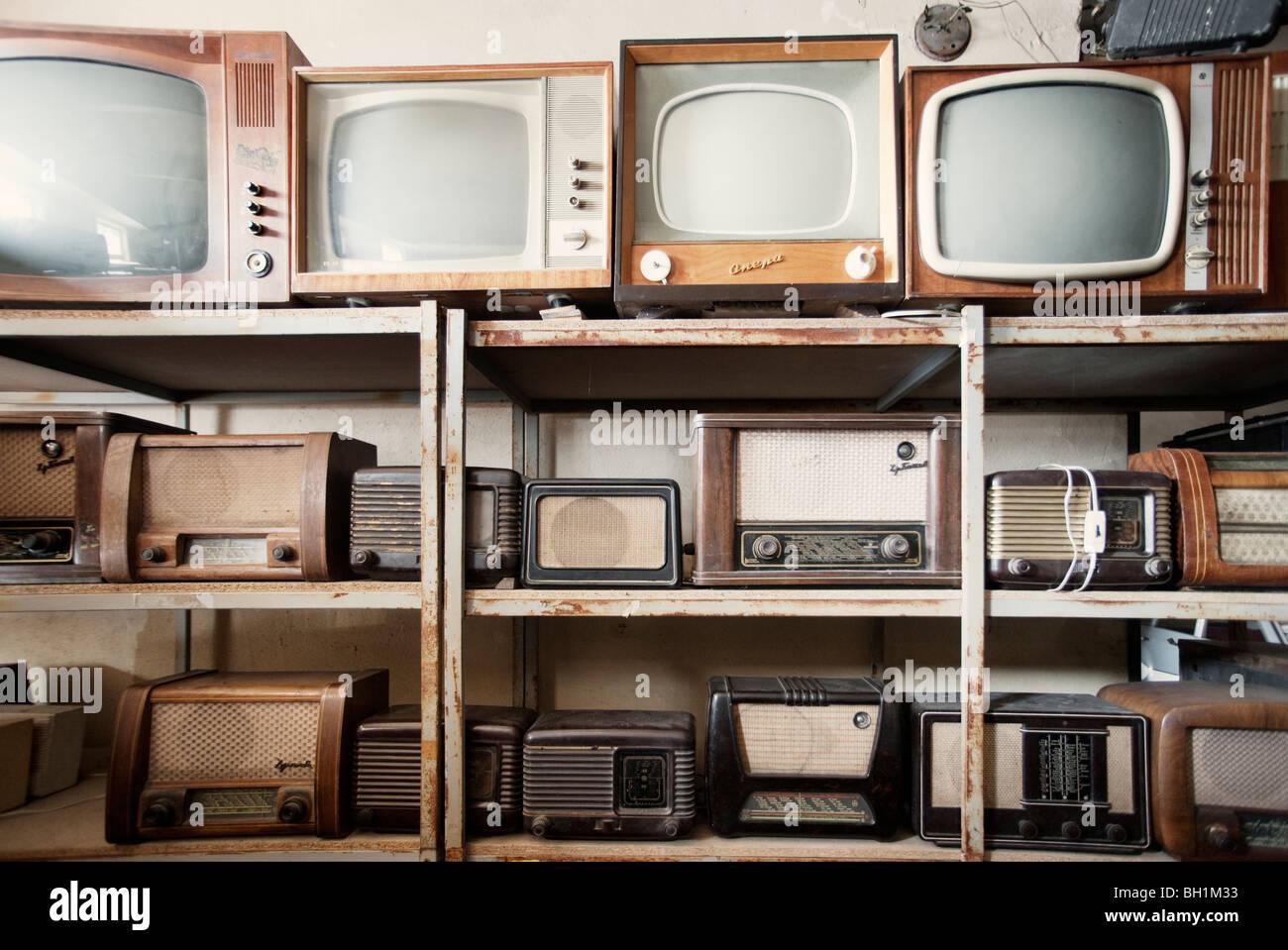 Ripiani di vecchie rotte apparecchi TV e radio Foto Stock