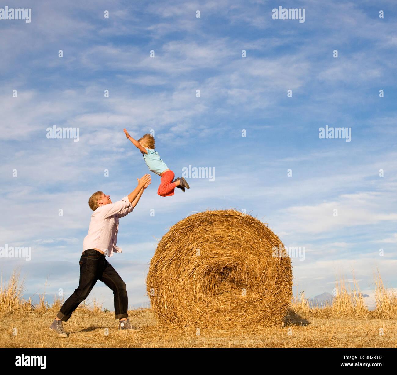 L'uomo la cattura del ragazzo che salta da balle di fieno Immagini Stock