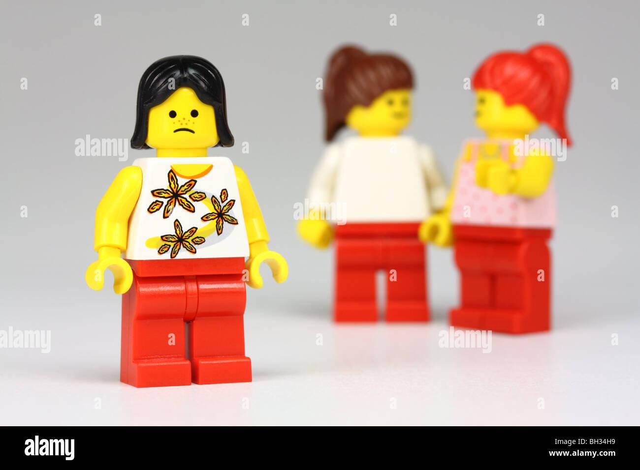 Infelice ragazza di lego, con altre 2 ragazze lego parlando della sua dietro la schiena : isolamento/bullismo concept Immagini Stock
