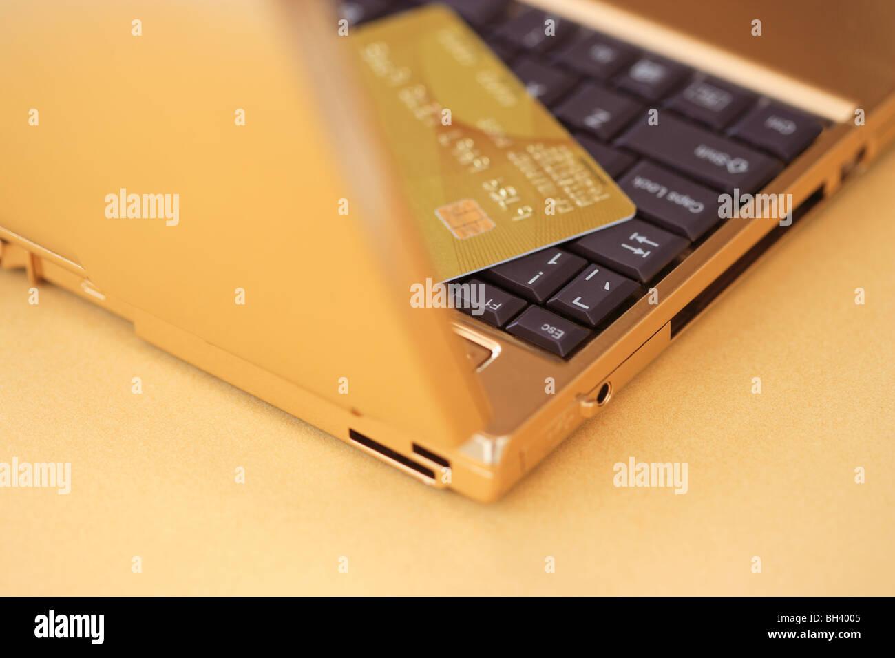 Un golden computer portatile e un golden carta di credito su un banco d'oro Immagini Stock