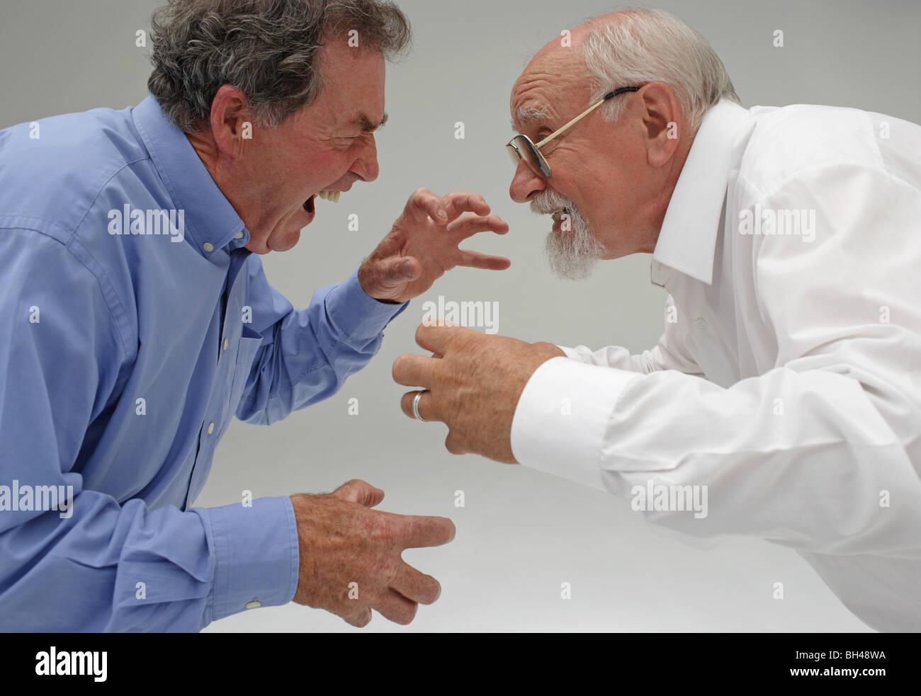 Due imprenditori senior circa per avere una lotta con espressioni aggressive. Immagini Stock