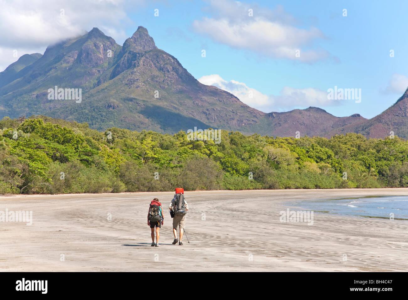Un uomo e una donna con il loro bambino escursione lungo Zoe Bay, Hinchinbrook Island, Queensland, Australia. Immagini Stock