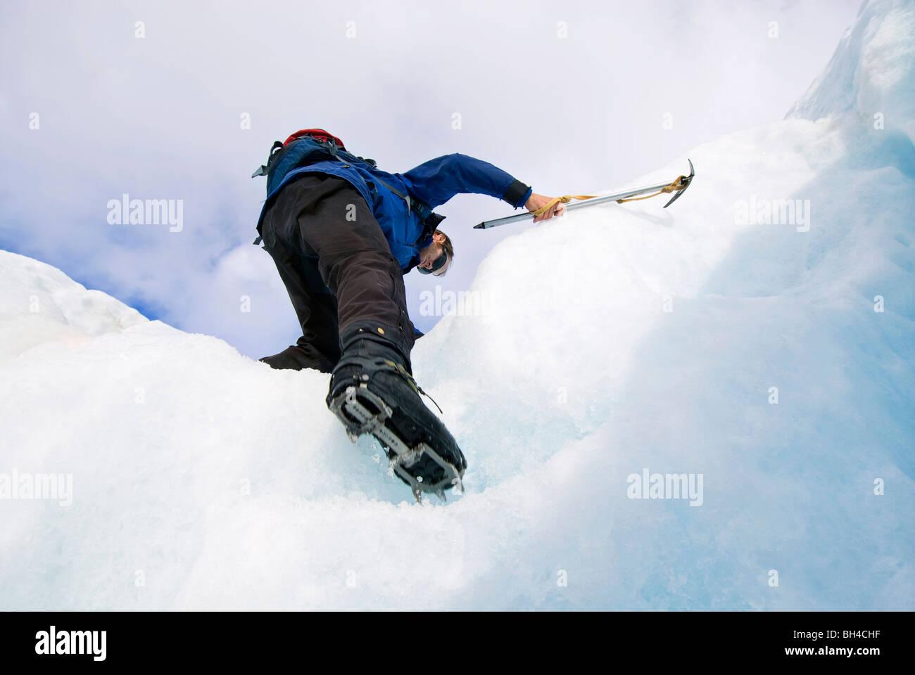 Un giovane uomo si arrampica passaggi su un ghiacciaio con i ramponi e una piccozza in Franz Josef, Nuova Zelanda. Immagini Stock