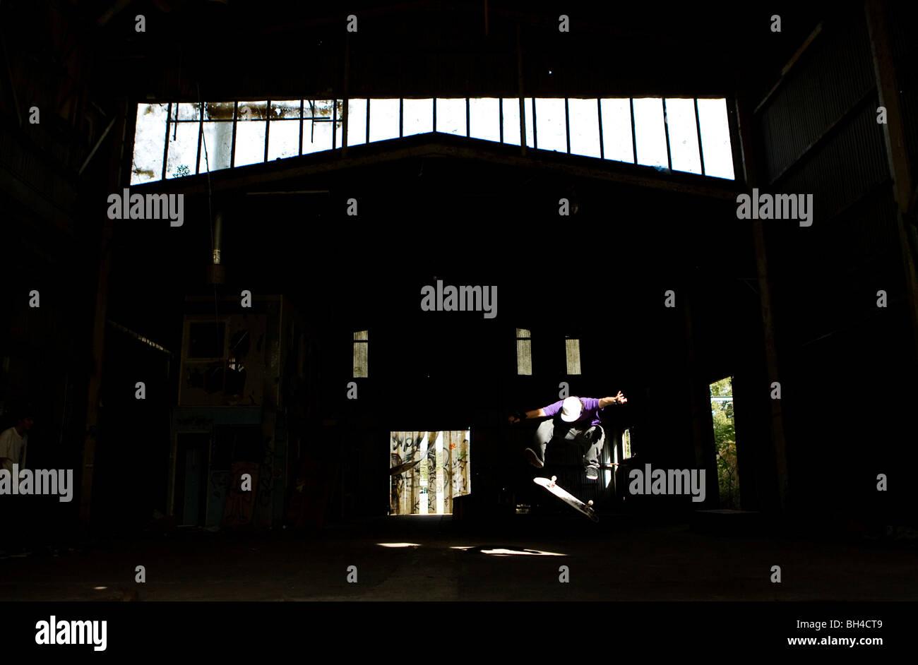 Un pattinatore esegue un kick flip in un magazzino abbandonato sulla costa centrale, Nuovo Galles del Sud, Australia. Immagini Stock