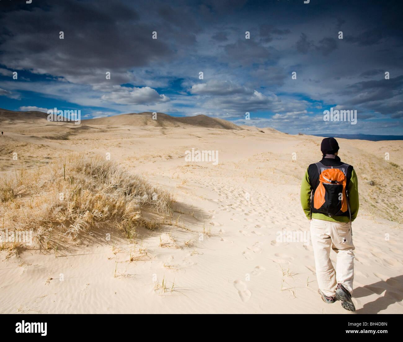Un uomo cammina sul naturale dune di sabbia sotto un cielo nuvoloso nel deserto di Mojave, California. Immagini Stock