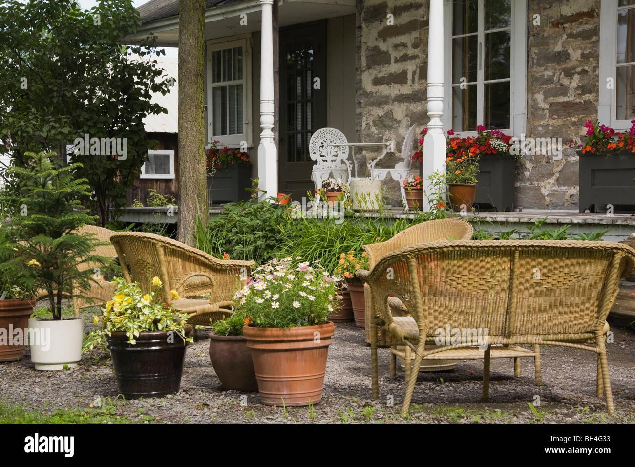 Vasi di piante e arredi di vimini nel cortile anteriore con Canadiana-stile Home in background, Laval, Québec Immagini Stock